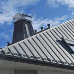 Modernes Stehfalz-Metalldach mit Dachfenster, Schneefang, Dachrinne, Dunstabzügen und mit Metall verkleidetem Schornstein